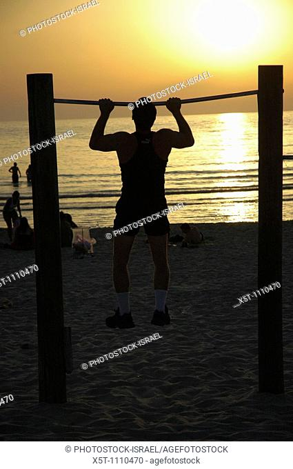 Israel, Tel Aviv, Physical work-out at sunset a man doing chin ups on the beach at sun set