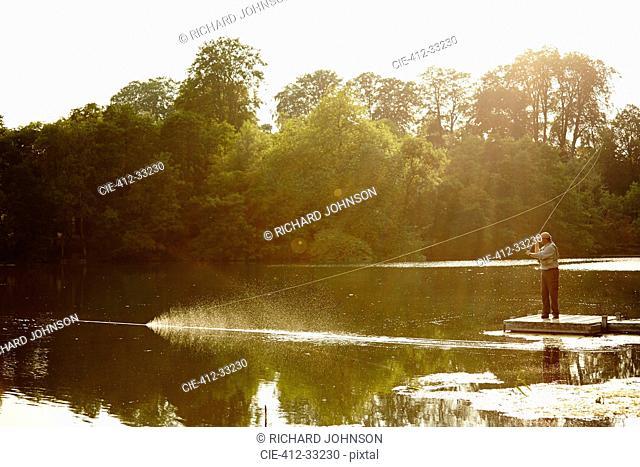 Senior man fly fishing on summer lake