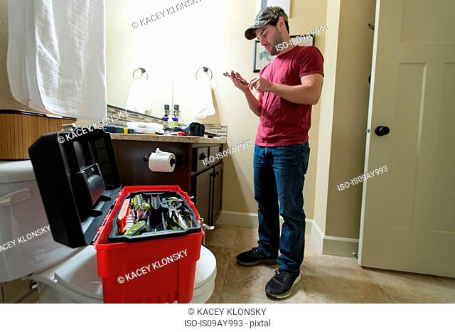 Man selecting tool to fix bathroom