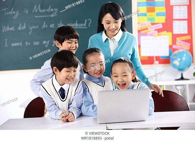 Teachers and students use computers in the classroom