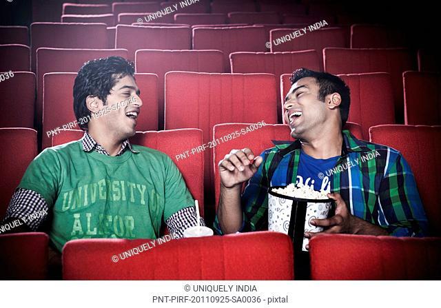 Friends enjoying movie and popcorn in a cinema hall