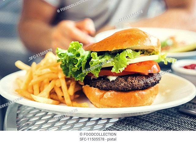 A cheeseburger and chips on a table in a restaurant