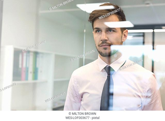 Young businessman in office looking through glass pane