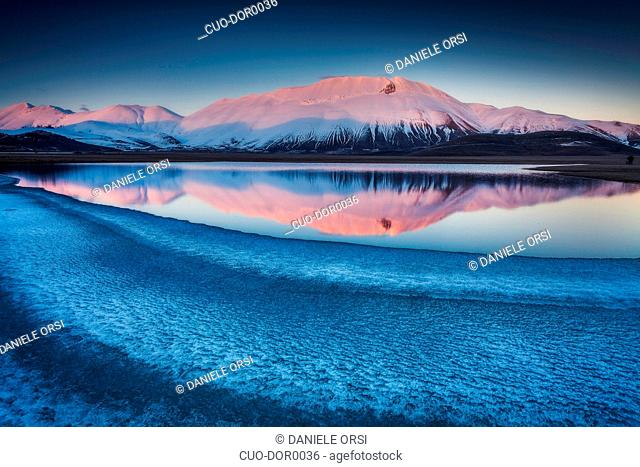Beautiful landscape in Castelluccio di Norcia during a frozen sunset on Mount Redentore reflected in the lake, Umbria, Italy, Europe