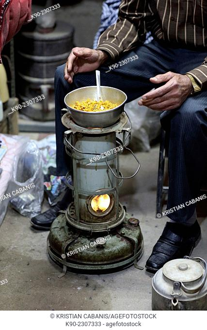 Bazari sitting in front of his meal prepared on a small oven, Bazar-e Bozorg in Esfahan, Isfahan, Iran, Asian