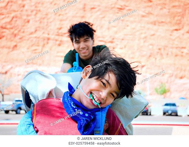 Teen boy pushing happy disabled biracial little brother in wheelchair, smiling and laughing, outdoors. cerebral palsy
