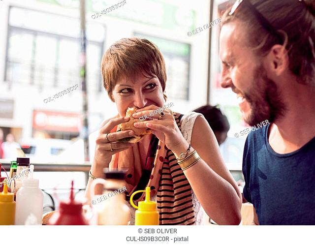 Couple eating burgers at sidewalk cafe, Cape Town, South Africa