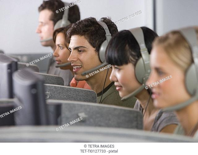 College students wearing headsets in computer lab