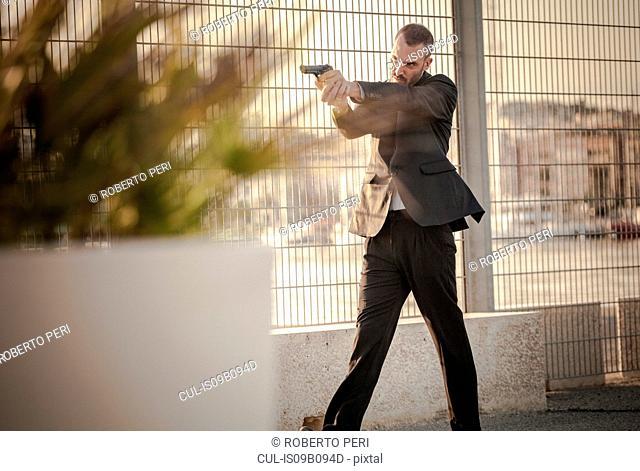Man in business attire walking in harbour poised with handgun, Cagliari, Sardinia, Italy