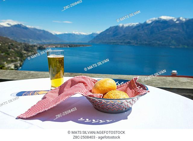 Table with bread and a glass beer and panoramic view over alpine lake Maggiore with snow-capped mountain and blue sky in a sunny day in Ticino, Switzerland