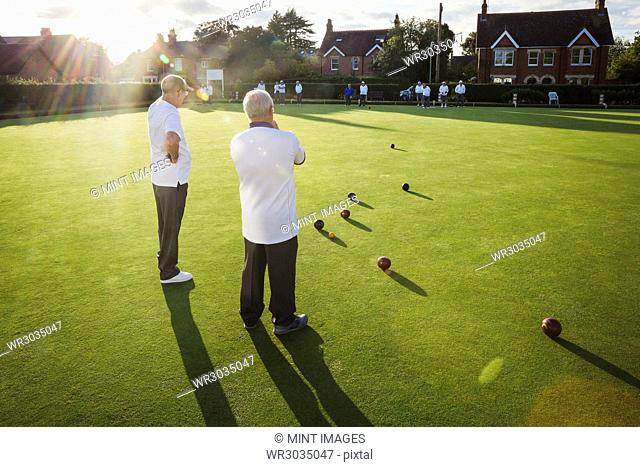 Two lawn bowls players, men standing discussing the game, and a clutch of lawn bowls on the playing surface
