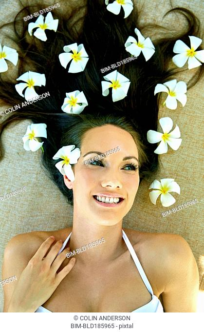 Pacific Islander woman laying with flowers in her hair