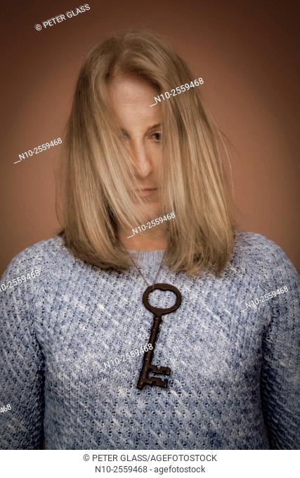 Blond woman with an old key hanging around her neck