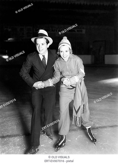 Young couple ice skating together All persons depicted are not longer living and no estate exists Supplier warranties that there will be no model release issues