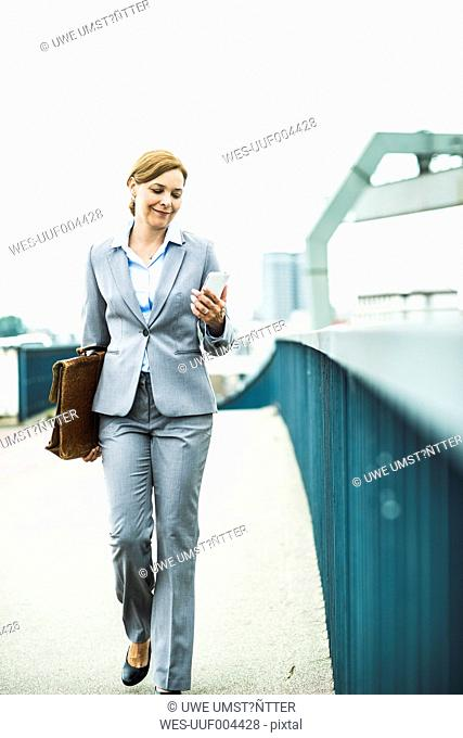 Businesswoman walking on bridge looking at cell phone