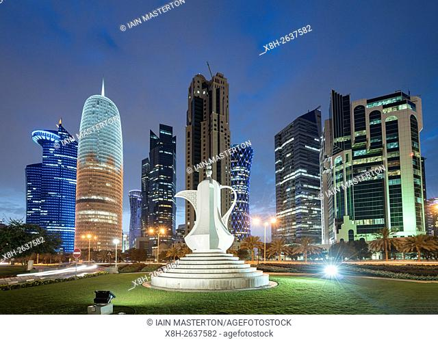 Night view of modern office towers and coffee pot sculpture in West Bay financial and business district in Doha Qatar