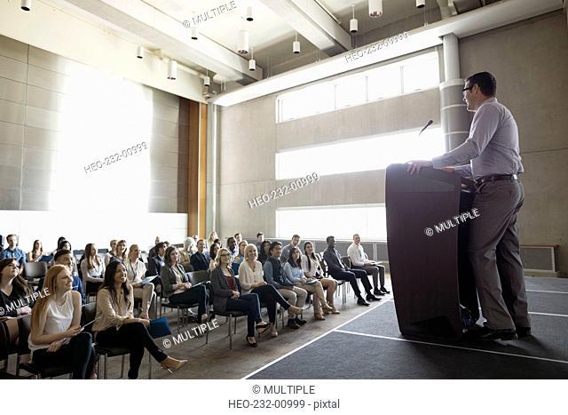 Professor at podium speaking to students in auditorium