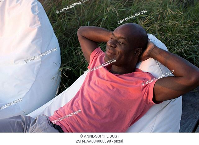Man relaxing outdoors with eyes closed
