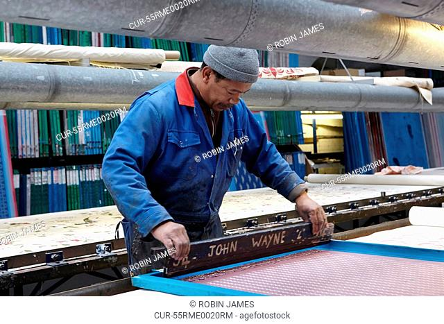 Man screen printing in textiles factory
