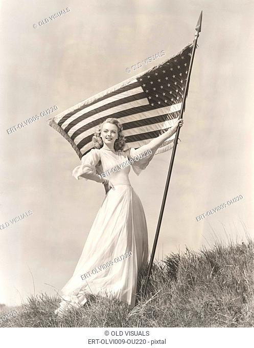 Proud woman in gown holding American flag on hill