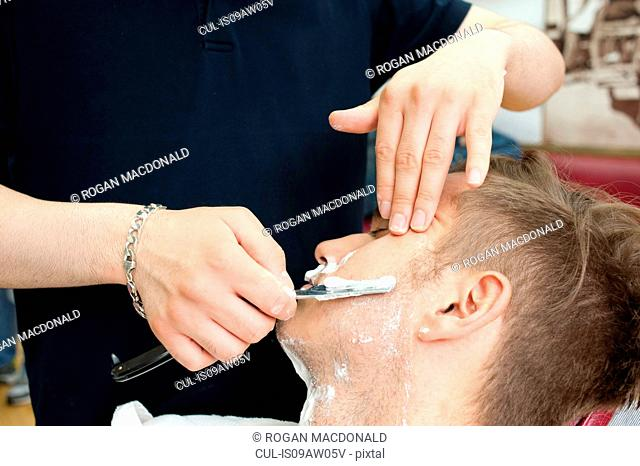 Cropped view of young man in barbershop shaving customer with straight razor