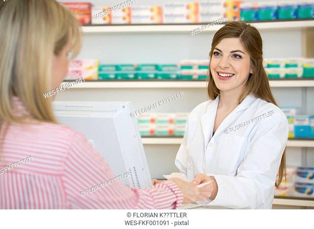 Portrait of smiling female pharmacist taking prescription from customer