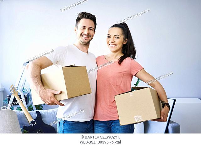 Portrait of happy couple moving in