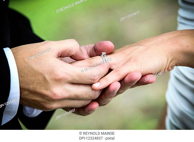A groom puts a ring onto his bride's finger during a marriage ceremony; Ontario, Canada