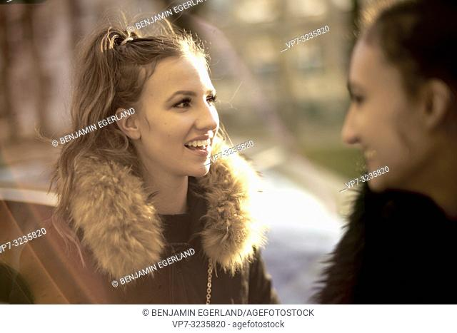 woman speaking to friend outdoors, in Munich, Germany