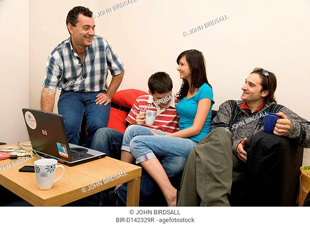 Group of friends in shared house relaxing and chatting
