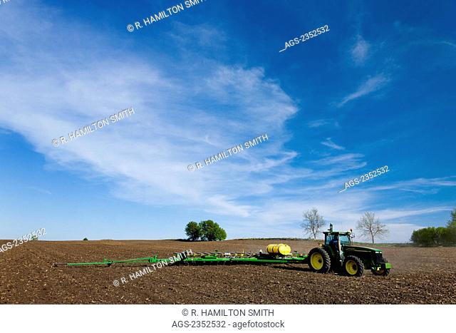 Agriculture - A John Deere tractor and 24-row planter planting corn in a conventionally tilled field / Minnesota, USA