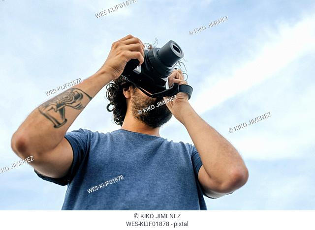 Panama, Bocas del Toro, Man with camera and camera tattoo on the arm
