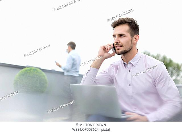 Two businessmen working on a rooftop terrace