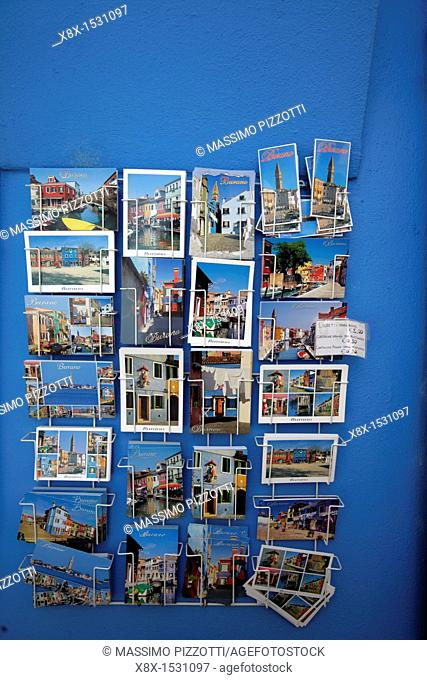 Postcards of Burano displayed on a blue wall, Venice, Italy