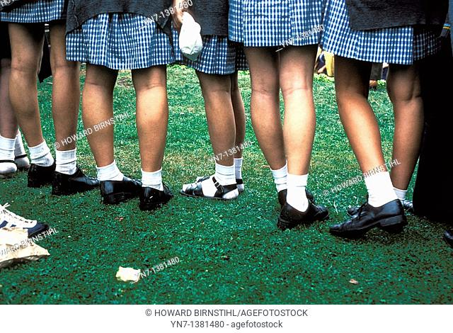 row of schoolgirls seen from behind from the waist down as they watch a sporting event on the school green