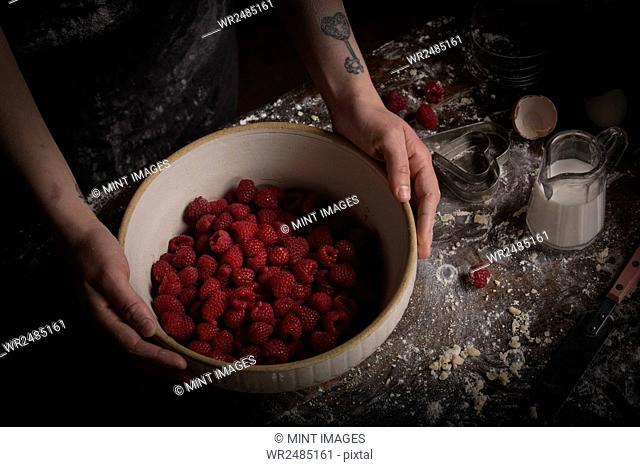 Valentine's Day baking. A woman preparing raspberries in a bowl