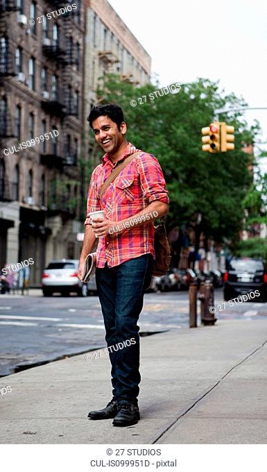 Young man walking along city street, smiling