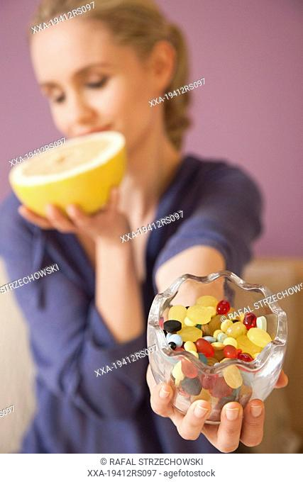 Woman with grapefruit and vitamins