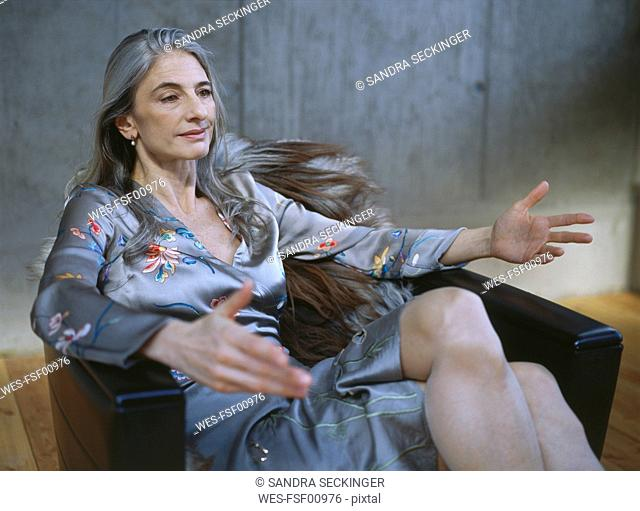 Portrait of mature woman sitting in armchair gesturing
