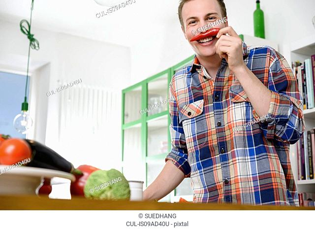 Man smelling red chili pepper