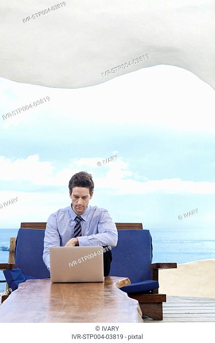A businessman sitting on a sofa and looking at a computer