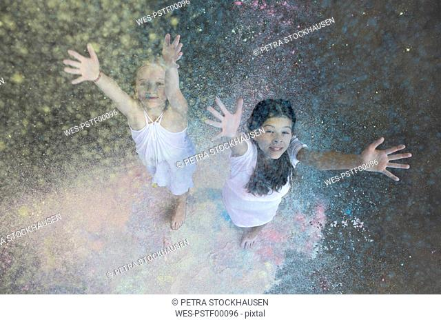 Portrait of two friends throwing colour powder in the air