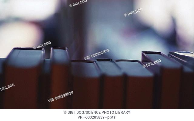 Panning shot of books on a shelf in a library