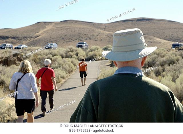 Tourists head back to their vehicles at a scenic outlook off Interstate 90 near Ellensburg, Washington, United States