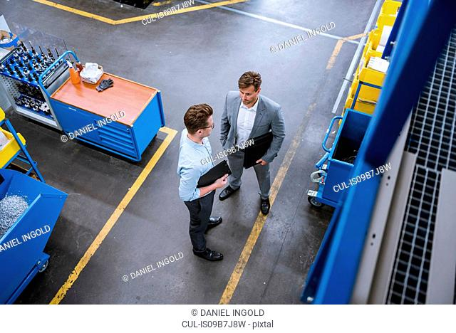 High angle view of two male managers with clipboards talking in factory