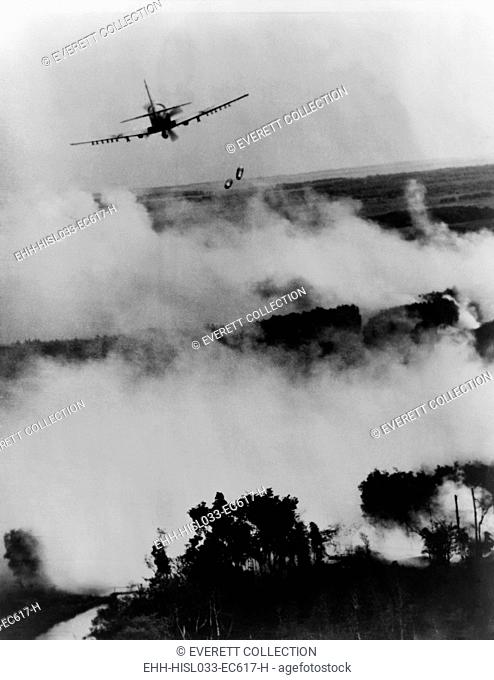 Vietnam War bombing. Two bombs fall from a Vietnamese Air Force A-1E Skyraider over a burning Viet Cong hideout near Cantho, South Viet Nam. 1967
