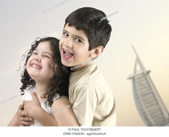 Children having fun on the beach in Dubai (Burj Al Arab hotel in background)