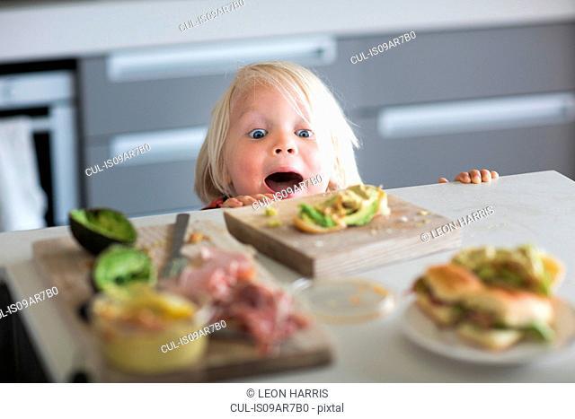 Boy peeking over kitchen counter
