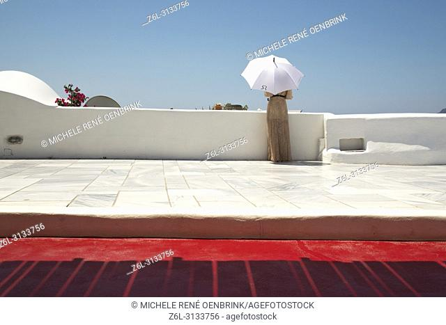 Tourist woman with umbrella for sun shade and Graphic design and architecture in Oia Santorini Greece