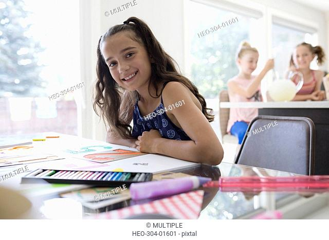 Portrait smiling girl coloring using stencils at dining table